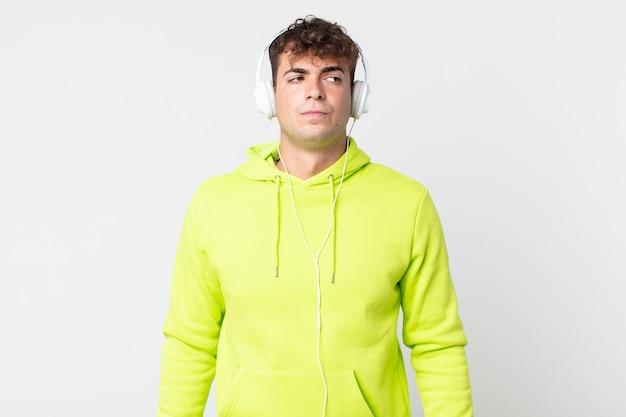 Młody przystojny mężczyzna czuje się smutny, zdenerwowany lub zły i patrzy w bok i słuchawki