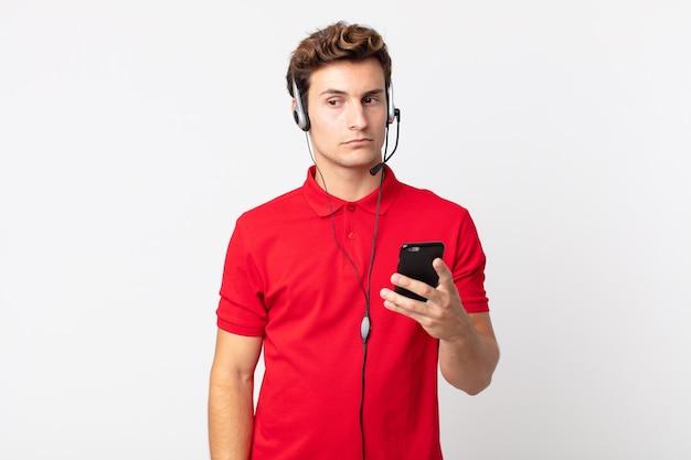 Młody przystojny mężczyzna czuje się smutny, zdenerwowany lub zły i patrzy w bok ze smartfonem i zestawem słuchawkowym