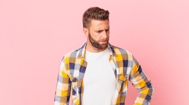 Młody przystojny mężczyzna czuje się smutny, zdenerwowany lub zły i patrzy w bok