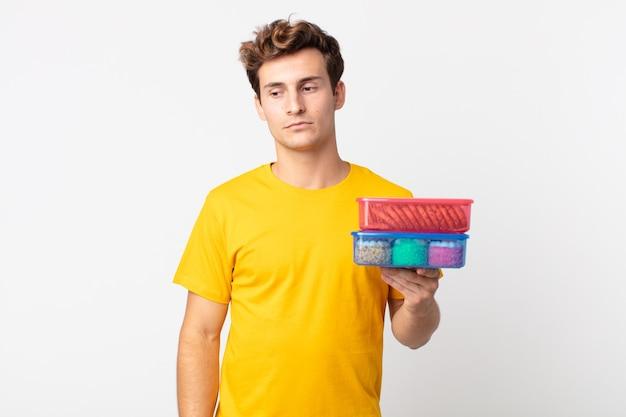 Młody przystojny mężczyzna czuje się smutny, zdenerwowany lub zły, patrzy w bok i trzyma pudełka na lunch