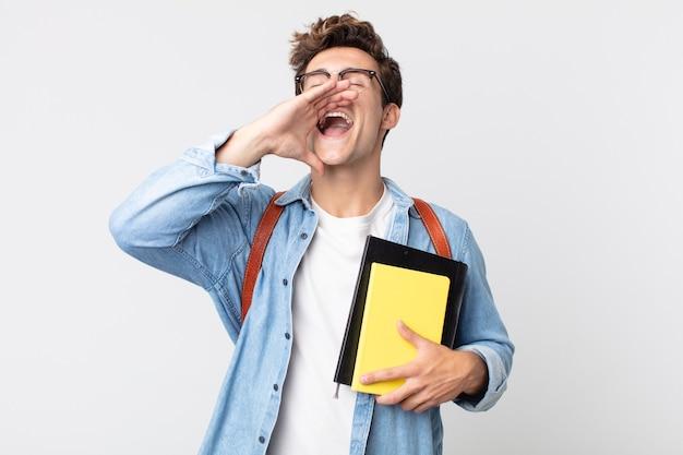 Młody przystojny mężczyzna czuje się szczęśliwy, dając wielki okrzyk z rękami przy ustach. koncepcja studenta uniwersytetu
