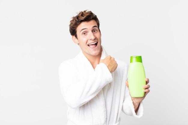 Młody przystojny mężczyzna czuje się szczęśliwy i mierzy się z wyzwaniem lub świętuje w szlafroku i trzyma butelkę szamponu