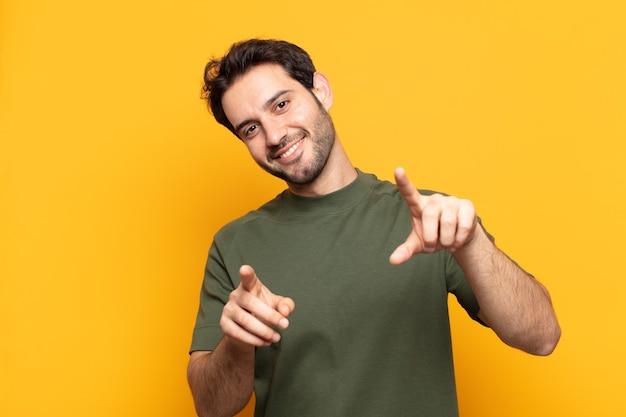 Młody przystojny mężczyzna czuje się szczęśliwy i pewny siebie, wskazując obiema rękami do przodu i śmiejąc się, wybierając ciebie