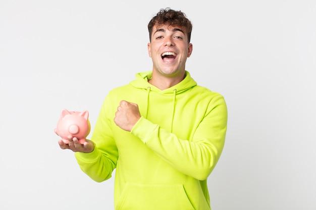 Młody przystojny mężczyzna czuje się szczęśliwy i stoi przed wyzwaniem lub świętuje i trzyma skarbonkę