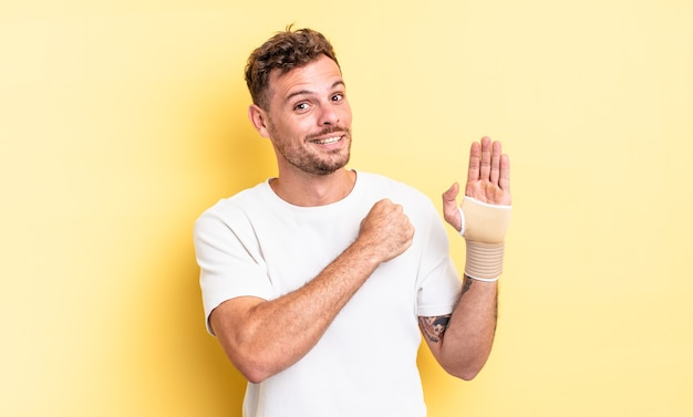 Młody przystojny mężczyzna czuje się szczęśliwy i stoi przed wyzwaniem lub świętuje. koncepcja bandaża ręcznego