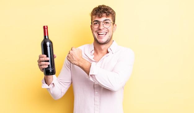 Młody przystojny mężczyzna czuje się szczęśliwy i stoi przed wyzwaniem lub świętuje. koncepcja butelki wina