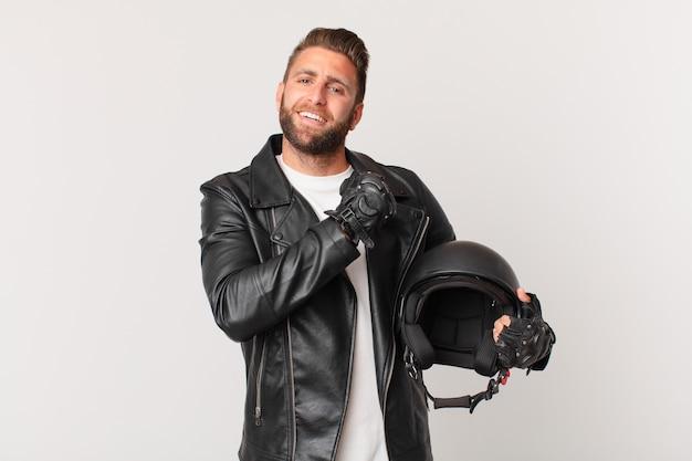 Młody przystojny mężczyzna czuje się szczęśliwy i stoi przed wyzwaniem lub świętuje. koncepcja kasku motocyklowego