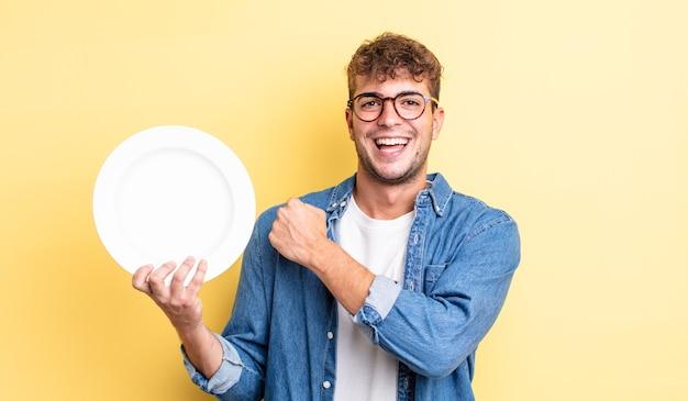 Młody przystojny mężczyzna czuje się szczęśliwy i stoi przed wyzwaniem lub świętuje. koncepcja pustego naczynia
