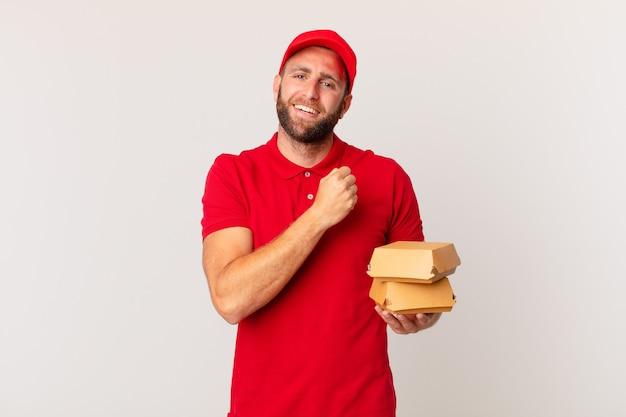Młody przystojny mężczyzna czuje się szczęśliwy i stoi przed wyzwaniem lub świętuje koncepcję dostarczania burgera