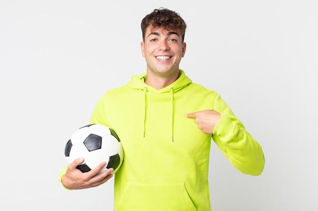Młody przystojny mężczyzna czuje się szczęśliwy i wskazuje na siebie z podekscytowaną i trzymającą piłkę nożną
