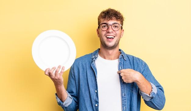 Młody przystojny mężczyzna czuje się szczęśliwy i wskazuje na siebie z podekscytowaniem. koncepcja pustego naczynia