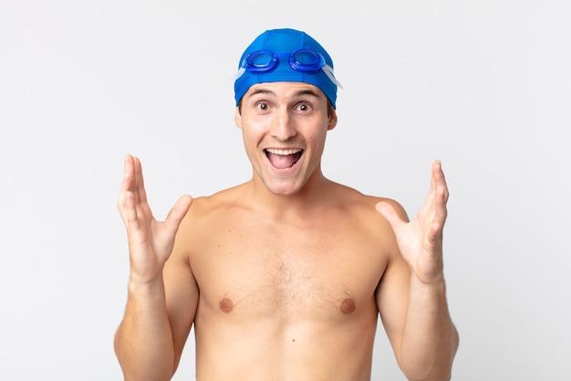 Młody przystojny mężczyzna czuje się szczęśliwy i zdumiony czymś niewiarygodnym. koncepcja pływaka