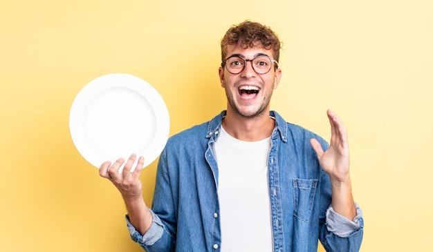 Młody przystojny mężczyzna czuje się szczęśliwy i zdumiony czymś niewiarygodnym. koncepcja pustego naczynia