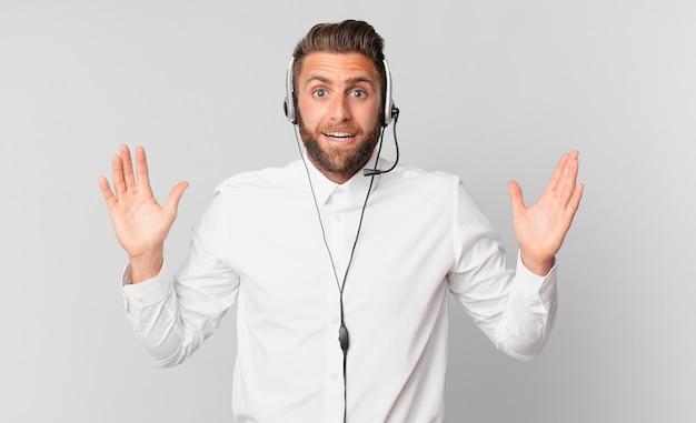 Młody przystojny mężczyzna czuje się szczęśliwy i zdumiony czymś niewiarygodnym. koncepcja telemarketingu