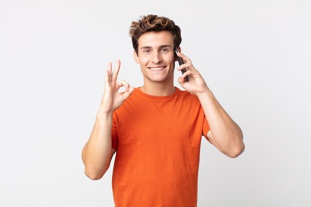 Młody przystojny mężczyzna czuje się szczęśliwy, okazując aprobatę dobrym gestem i rozmawiając ze smartfonem