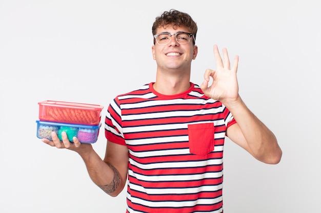 Młody przystojny mężczyzna czuje się szczęśliwy, okazując aprobatę dobrym gestem i trzymający pudełka na lunch