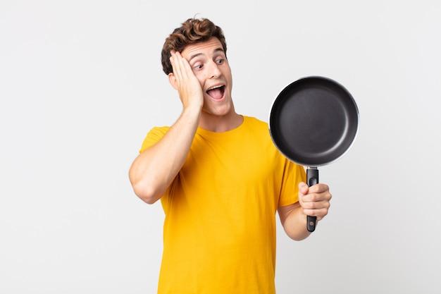 Młody przystojny mężczyzna czuje się szczęśliwy, podekscytowany i zaskoczony i trzyma patelnię kucharską