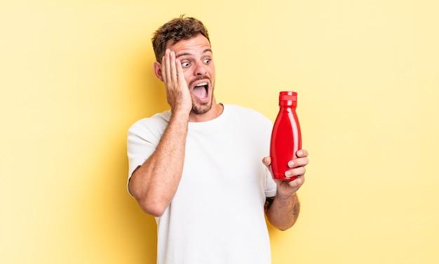 Młody przystojny mężczyzna czuje się szczęśliwy, podekscytowany i zaskoczony. koncepcja ketchupu