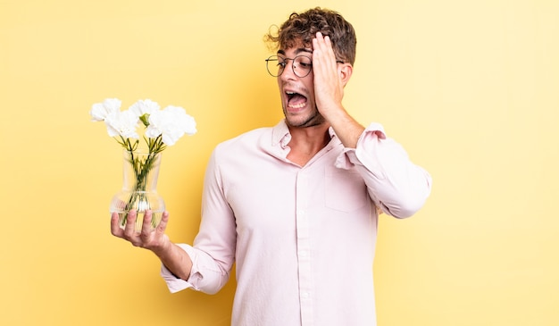 Młody przystojny mężczyzna czuje się szczęśliwy, podekscytowany i zaskoczony. koncepcja kwiaty