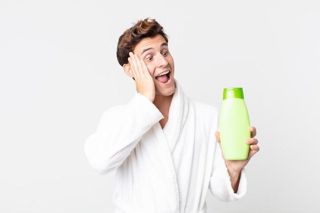 Młody przystojny mężczyzna czuje się szczęśliwy, podekscytowany i zaskoczony szlafrokiem i trzymając butelkę szamponu
