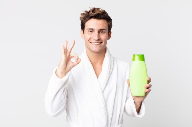 Młody przystojny mężczyzna czuje się szczęśliwy, pokazując aprobatę dobrym gestem ze szlafrokiem i trzymając butelkę szamponu