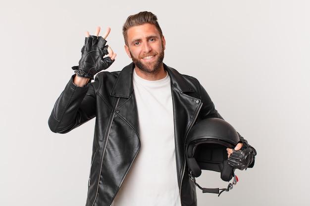 Młody przystojny mężczyzna czuje się szczęśliwy, pokazując aprobatę w porządku gestem. koncepcja kasku motocyklowego