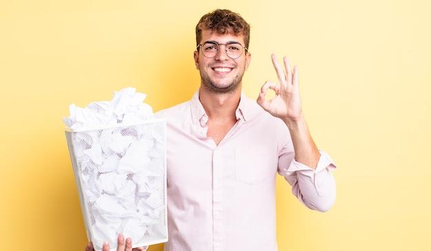 Młody przystojny mężczyzna czuje się szczęśliwy, pokazując aprobatę w porządku gestem. koncepcja śmieci z kulkami papierowymi