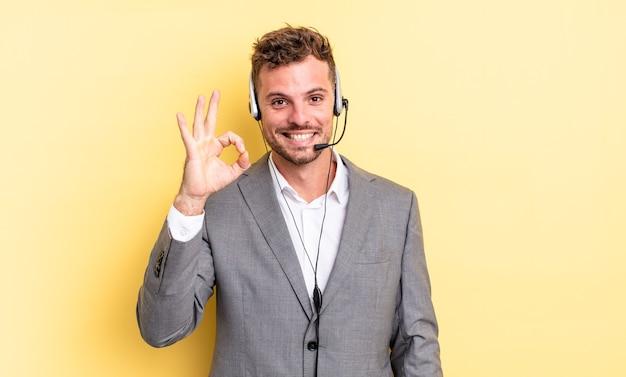 Młody przystojny mężczyzna czuje się szczęśliwy, pokazując aprobatę w porządku gestem. koncepcja telemarketera