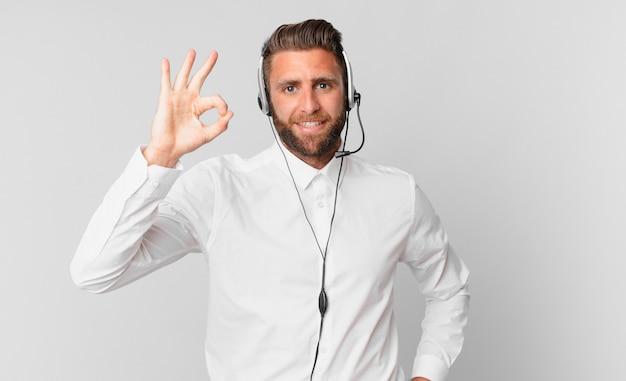 Młody przystojny mężczyzna czuje się szczęśliwy, pokazując aprobatę w porządku gestem. koncepcja telemarketingu