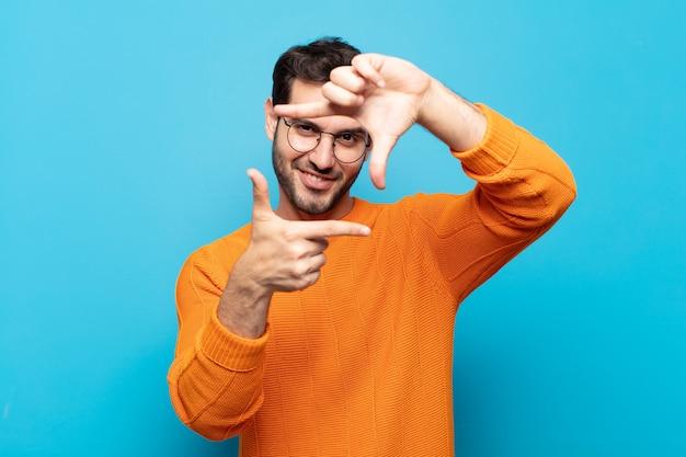 Młody przystojny mężczyzna czuje się szczęśliwy, przyjazny i pozytywny, uśmiecha się i robi z rąk portret lub ramkę na zdjęcia