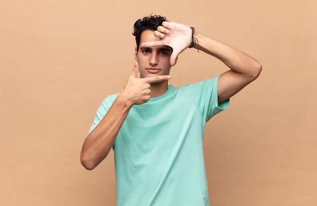 Młody przystojny mężczyzna czuje się szczęśliwy, przyjazny i pozytywny, uśmiechając się i robiąc portret lub ramkę na zdjęcia rękami