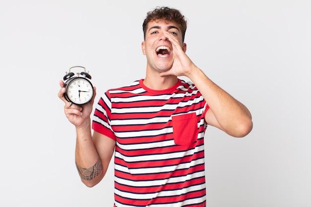 Młody przystojny mężczyzna czuje się szczęśliwy, wydając wielki okrzyk z rękami przy ustach i trzymając budzik