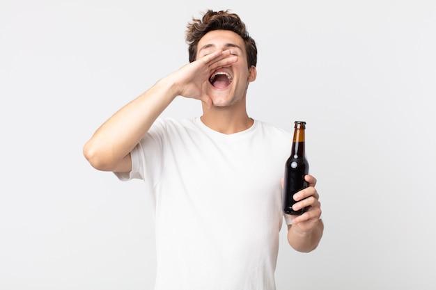 Młody przystojny mężczyzna czuje się szczęśliwy, wydając wielki okrzyk z rękami przy ustach i trzymając butelkę piwa