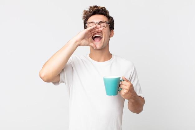Młody przystojny mężczyzna czuje się szczęśliwy, wydając wielki okrzyk z rękami przy ustach i trzymając filiżankę kawy