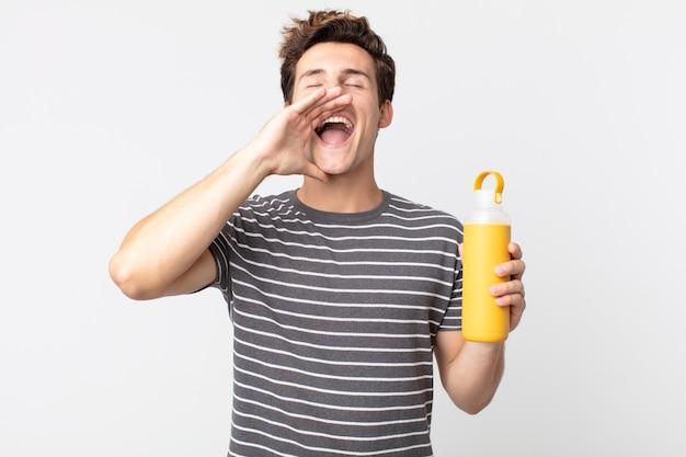 Młody przystojny mężczyzna czuje się szczęśliwy, wydając wielki okrzyk z rękami przy ustach i trzymając termos z kawą