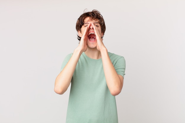Młody przystojny mężczyzna czuje się szczęśliwy, wydając wielki okrzyk z rękami przy ustach