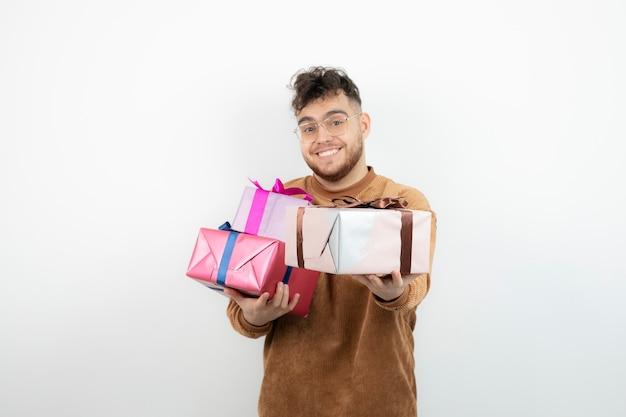 Młody przystojny mężczyzna czuje się szczęśliwy z pudełkami prezentów.