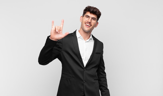 Młody przystojny mężczyzna czuje się szczęśliwy, zabawny, pewny siebie, pozytywny i zbuntowany, robi ręką znak rocka lub heavy metal