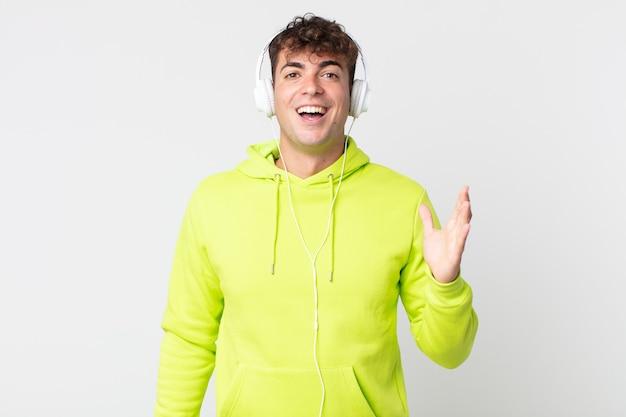 Młody przystojny mężczyzna czuje się szczęśliwy, zaskoczony, gdy realizuje rozwiązanie lub pomysł i słuchawki