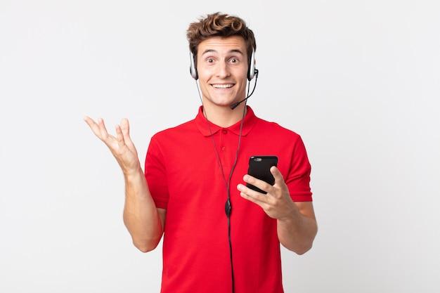 Młody przystojny mężczyzna czuje się szczęśliwy, zaskoczony, gdy realizuje rozwiązanie lub pomysł za pomocą smartfona i zestawu słuchawkowego