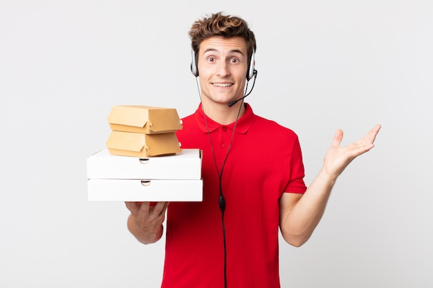 Młody przystojny mężczyzna czuje się szczęśliwy, zaskoczony, realizując rozwiązanie lub pomysł. koncepcja fast foodów na wynos