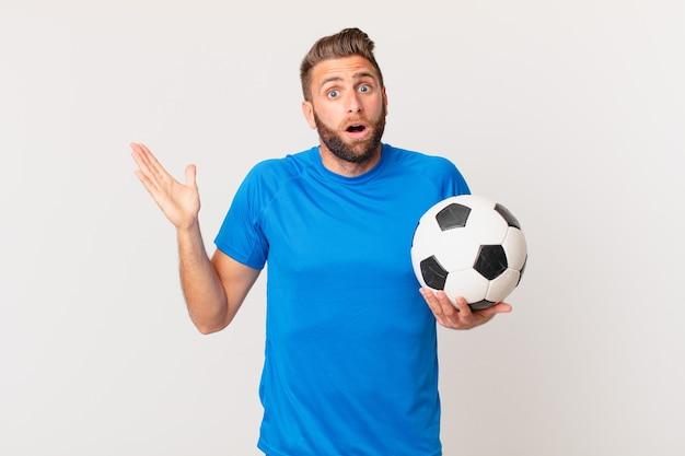 Młody przystojny mężczyzna czuje się szczęśliwy, zaskoczony, realizując rozwiązanie lub pomysł. koncepcja piłki nożnej