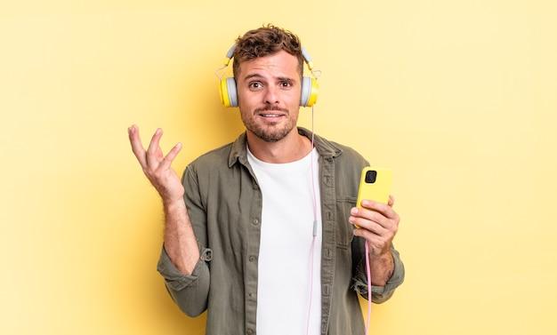 Młody przystojny mężczyzna czuje się szczęśliwy, zaskoczony, realizując rozwiązanie lub pomysł na słuchawki i koncepcję smartfona