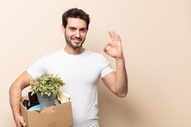 Młody przystojny mężczyzna czuje się szczęśliwy, zrelaksowany i zadowolony, okazując aprobatę dobrym gestem, uśmiechając się