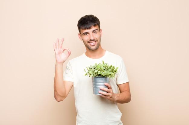 Młody przystojny mężczyzna czuje się szczęśliwy, zrelaksowany i zadowolony, pokazując zatwierdzenie z dobrym gestem, uśmiechając się, trzymając roślinę
