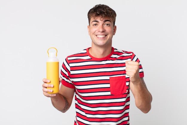 Młody przystojny mężczyzna czuje się w szoku, śmieje się i świętuje sukces i trzyma termos z kawą