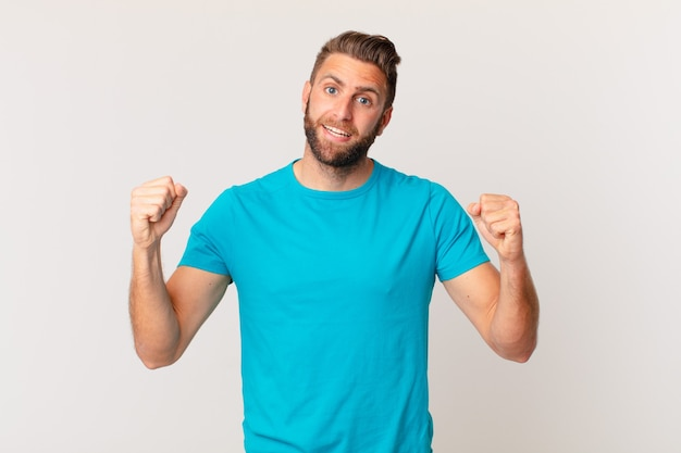 Młody przystojny mężczyzna czuje się w szoku, śmieje się i świętuje sukces. koncepcja fitness