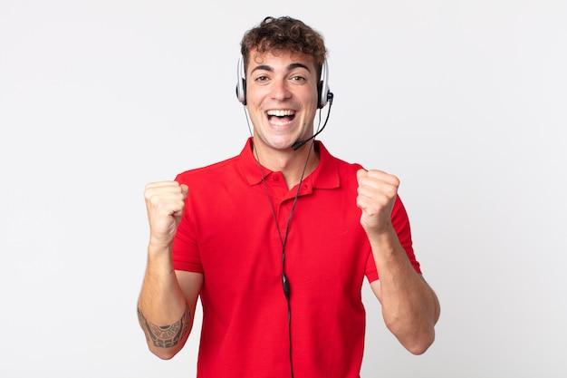 Młody przystojny mężczyzna czuje się w szoku, śmieje się i świętuje sukces. koncepcja telemarketera