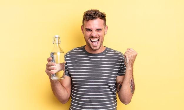 Młody przystojny mężczyzna czuje się w szoku, śmieje się i świętuje sukces. koncepcja wody