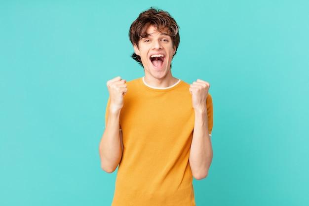 Młody przystojny mężczyzna czuje się w szoku, śmieje się i świętuje sukces